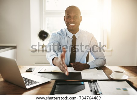 Smiling young African executive extending his arm in a handshake while sitting at his desk in an office