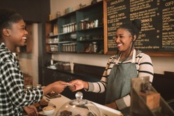 Smiling young African female barista standing behind a counter in a cafe taking a credit card from a customer to pay for a coffee