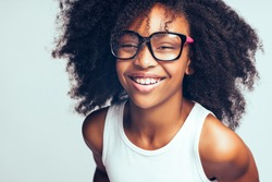 Smiling young African girl with long curly hair wearing glasses while standing by herself against a gray background