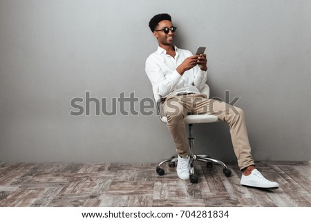 Smiling young african man sitting in a chair and holding mobile phone isolated over gray background