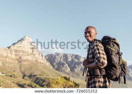Smiling young African man wearing a backpack standing on a trail looking at the view while hiking alone in the hills on a sunny day