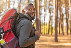 Smiling young african man wearing backpack standing on autumn forest trail, looking aside, hiking alone, copy space