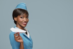 Smiling young african stewardess holding a paper airplane in her hand. Blue background.