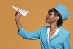 Smiling young african stewardess holding a paper airplane in her hand. Orange background.