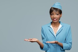 Smiling young african stewardess shows a welcome gesture. Blue background.