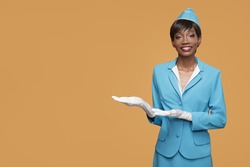 Smiling young african stewardess shows a welcome gesture. Orange background.