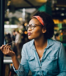Smiling young African woman deep in thought and looking through a window while sitting alone in a cafe enjoying a meal