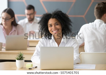 Smiling young african woman employee, office worker or student looking at camera in coworking, happy millennial black professional manager or intern working studying with laptop, head shot portrait