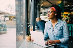 Smiling young African woman looking through a window while sitting alone in cafe working on a laptop and wearing headphones