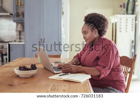 Smiling young African woman sitting alone at her kitchen table while working online from home with a laptop - Shutterstock ID 726031183