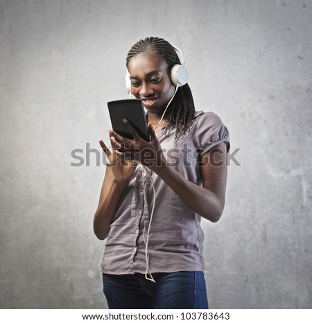 Smiling young african woman using a tablet - stock photo