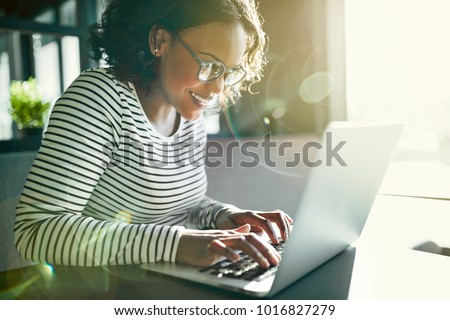 Smiling young African woman wearing glasses working online with a laptop while sitting alone at a table
