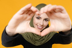 Smiling young arabian muslim woman in hijab black green clothes showing shape heart with hands heart-shape sign isolated on yellow color background studio portrait. People religious lifestyle concept