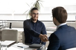 Smiling young Arabic businessman in glasses handshake male business partner get acquainted greeting at meeting, happy Arabian man shake hand of colleague close deal in office, partnership concept