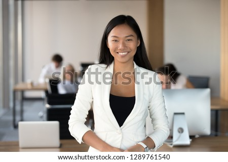 Smiling young asian business woman looking at camera, happy chinese employee worker, team leader, coach or corporate manager posing in office, millennial korean professional head shot portrait