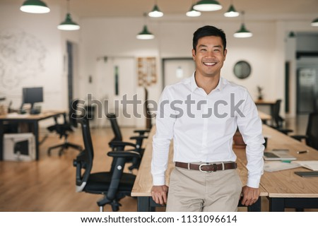 Smiling young Asian businessman leaning against a table while working alone in a large modern office