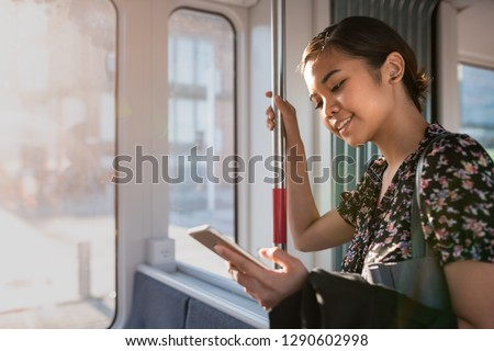 Smiling young Asian businesswoman catching up on social media while riding on a train in the city during her morning commute