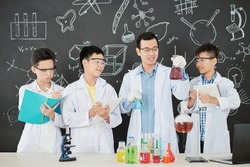 Smiling young Asian chemistry teacher showing what liquids he is going to mix to show chemical reaction to students