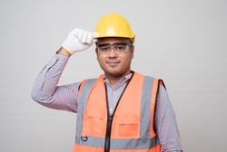 Smiling young asian civil engineer wearing helmet hard hat standing on isolated white background. Mechanic service concept.