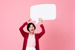 Smiling young Asian woman holding empty speech bubble in pink studio background