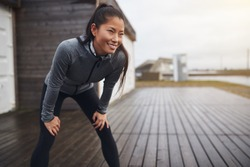 Smiling young Asian woman in exercise clothing standing with her hands on her knees while taking a break from a run on an overcast day