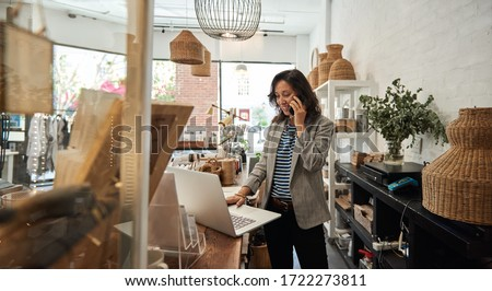 Smiling young Asian woman standing behind a counter in her stylish boutique working on a laptop and talking on a cellphone