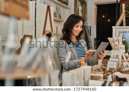 Smiling young Asian woman using a digital tablet while standing behind a counter in her stylish boutique