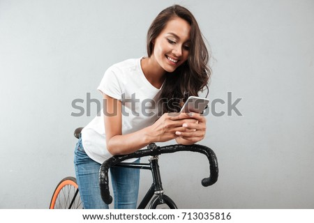 Smiling young asian woman using mobile phone while sitting on a bicycle isolated over gray background #713035816