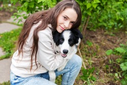Smiling young attractive woman embracing cute puppy dog border collie in summer city park outdoor background. Girl huging new lovely member of family. Pet care and animals concept