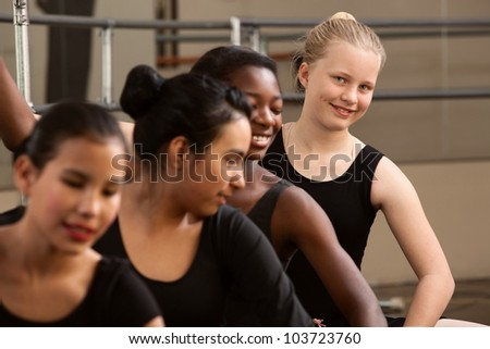 Smiling young ballet student with her classmates