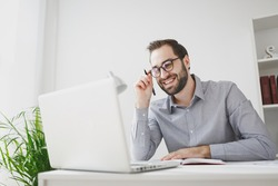 Smiling young bearded business man in gray shirt glasses sitting at desk in light office on white wall background. Achievement business career concept. Working on laptop pc computer, holding pen