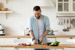 Smiling young bearded man cooking salad, cutting fresh vegetables in modern kitchen, happy satisfied male preparing vegetarian snacks, food for dinner or party, enjoying leisure time, hobby