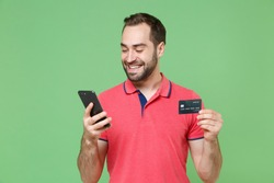 Smiling young bearded man guy in casual red pink t-shirt posing isolated on green background studio portrait. People lifestyle concept. Mock up copy space. Using mobile phone, hold credit bank card