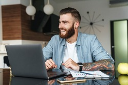 Smiling young bearded man working on laptop computer while sitting at the kitchen table