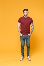 Smiling young bearded tattooed man guy in casual t-shirt black cap posing isolated on yellow wall background studio portrait. People lifestyle concept. Mock up copy space. Holding hands in pockets