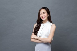 Smiling young beautiful Asian businesswoman looking at camera and doing arm crossed gesture in isolated studio gray background
