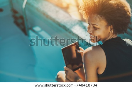 Smiling young beautiful Brazilian female with curly afro hair is sitting on the edge of small swimming pool and holding her digital pad; copy space for text or your advertising; teal and orange colors