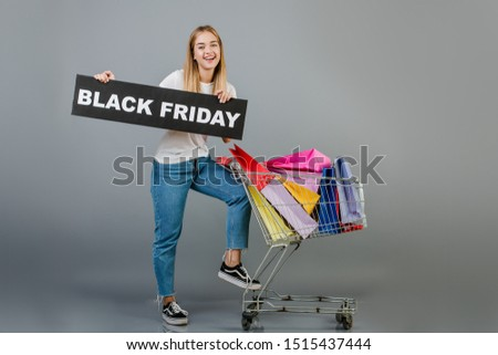 smiling young beautiful girl with black friday sign and pushcart full of colorful shopping bags isolated over grey