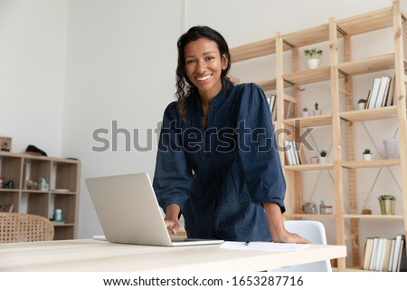 Smiling young biracial woman standing at table with computer, looking at camera. Happy african american business woman company employee manager professional posing for photo alone in modern office.