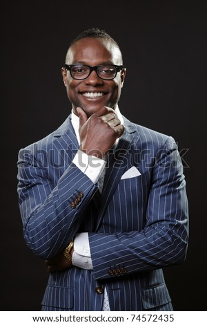 Smiling young black business man wearing suit and glasses.