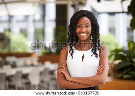 Smiling young black businesswoman with arms crossed