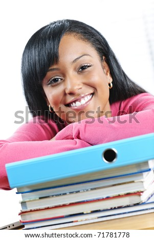 Smiling young black female student with textbooks at desk