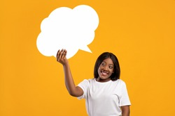 Smiling young black lady with blank communication bubble, yellow studio background. Cheerful pretty african american woman holding empty clipart, sharing her thoughts or ideas, copy space