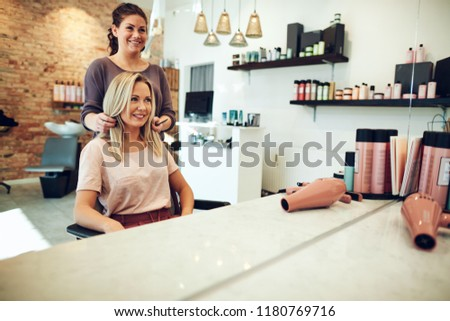 Smiling young blonde woman looking at her hair in a salon mirror during an appointment with her hairstylist