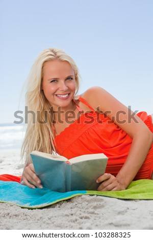 Smiling young blonde woman lying on the side while reading a book on the beach
