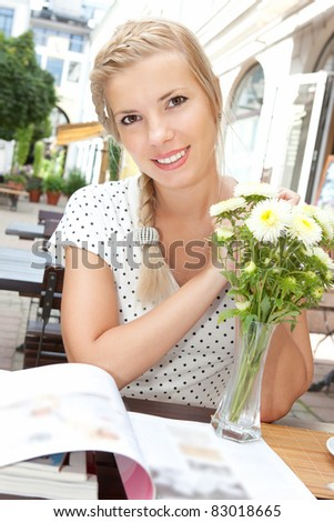 Smiling young blonde woman reading a magazine outdoors