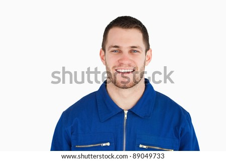 Smiling young blue collar worker against a white background