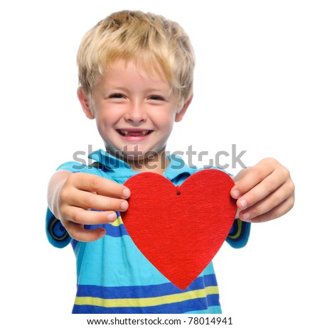 Smiling young boy holds out a red heart , isolated on white