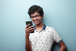 Smiling young boy of Indian origin looking at his mobile phone