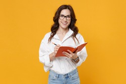 Smiling young brunette business woman in white shirt glasses isolated on yellow background studio portrait. Achievement career wealth business concept. Mock up copy space. Writing notes in notebook